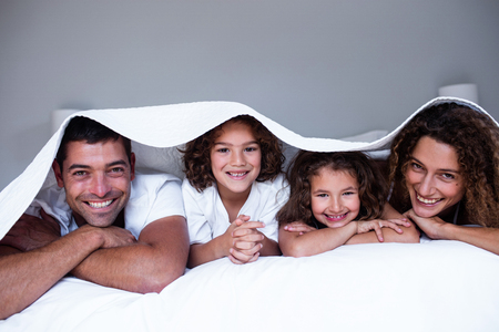bedsheet: Portrait of happy family lying under a bedsheet at home Stock Photo