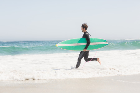 escapism: Man in wetsuit carrying a surfboard and running towards sea