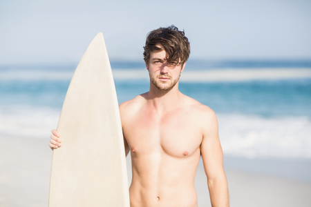 escapism: Handsome man holding surfboard on the beach on a sunny day