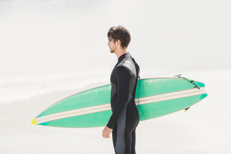 escapism: Man holding surfboard on the beach on a sunny day Stock Photo