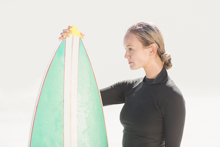 wetsuit: Woman in wetsuit holding a surfboard on a sunny day