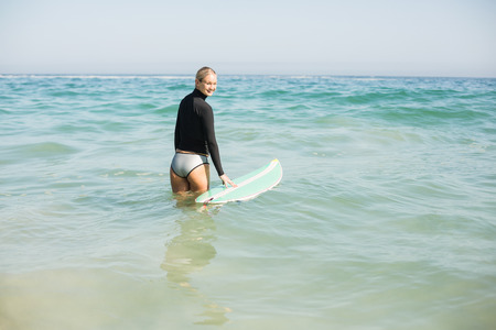 escapism: Woman in wetsuit holding a surfboard on the beach at sunny day Stock Photo