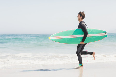 wetsuit: Man in wetsuit carrying a surfboard and running towards sea