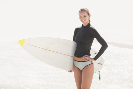 wetsuit: Woman in wetsuit holding a surfboard on the beach on a sunny day