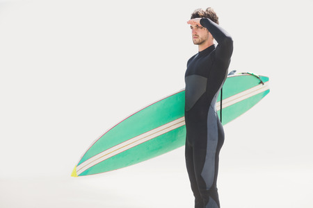 shielding: Man with surfboard shielding eyes at beach on sunny day