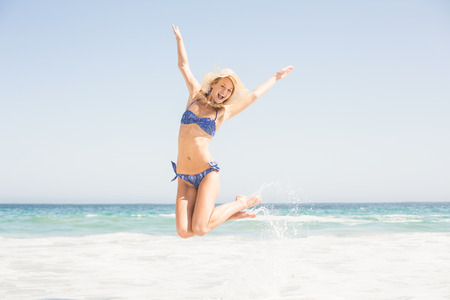 outstretch: Carefree woman in bikini jumping on the beach with arms outstretch