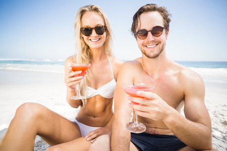 portarit: Portarit of happy young couple sitting on the beach and having cocktail glasses Stock Photo