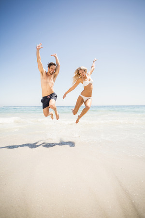 outstretch: Happy couple jumping on the beach with arms outstretch Stock Photo