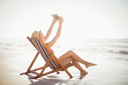 mujer desnuda sentada: Mujer que habla una autofoto en una tableta digital en un día soleado