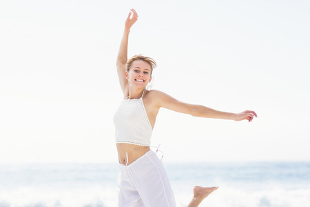 outstretch: Carefree woman in jumping on the beach with arms outstretch