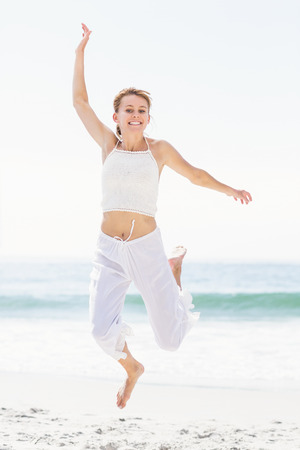 the carefree: Carefree woman in jumping on the beach with arms outstretch