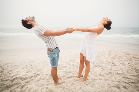 backwards: Happy couple holding hands and bending backwards on the beach Stock Photo