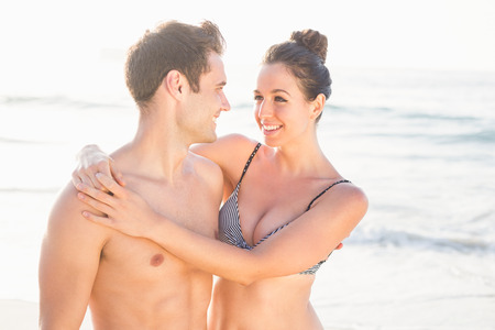 bikini couple: Happy couple embracing on the beach on a sunny day Stock Photo