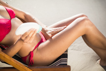 escapism: Mid-section of woman sitting on armchair and applying sunscreen lotion on the beach Stock Photo