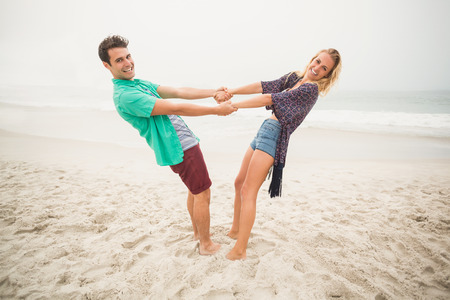 backwards: Portrait of happy couple holding hands and bending backwards on the beach