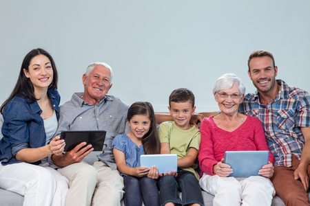 family sofa: Portrait of happy family sitting on sofa using a digital tablet in living room Stock Photo