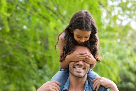 shoulder carrying: Father carrying her daughter on shoulder in the park