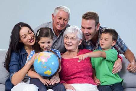 family sofa: Happy family sitting on sofa holding a globe in living room