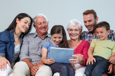 Happy family sitting on sofa using a digital tablet in living room