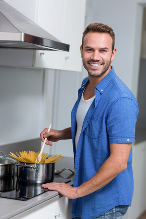 Young man cooking spaghetti in the kitchen