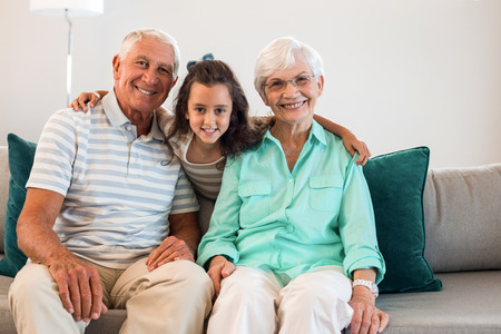 grand father: Portrait of grandmother and grand father with their granddaughter sitting on sofa in living room Stock Photo