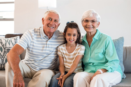 grand father: Portrait of Grandmother and grand father with their granddaughter sitting on sofa in living room