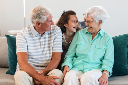 grand father: Grandmother and grand father with their granddaughter sitting on sofa in living room