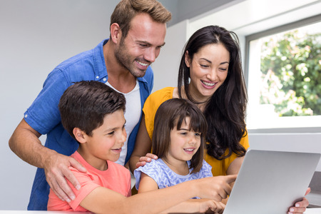 interacting: Happy family interacting using laptop in their living room Stock Photo