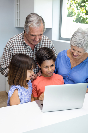grand parents: Grand parents and grandchildren interacting using laptop in their living room
