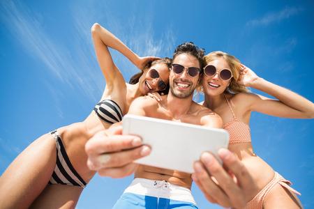 circulo de personas: amigos felices que se divierten en la playa en un día soleado