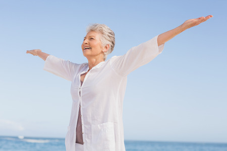 Casual senior woman with arms outstretched standing at the beach