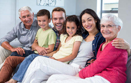 Portrait of family sitting on sofa and smiling in living room