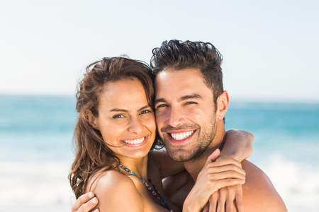 cuddling: Happy couple hugging on the beach on a sunny day