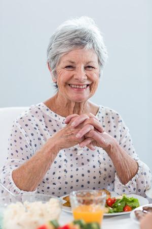 tomando refresco: Mujer mayor que come el desayuno por la mañana
