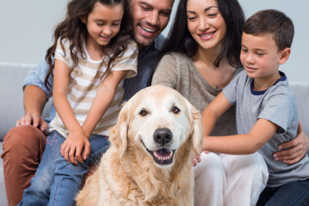 family  room: Family petting dog in living room