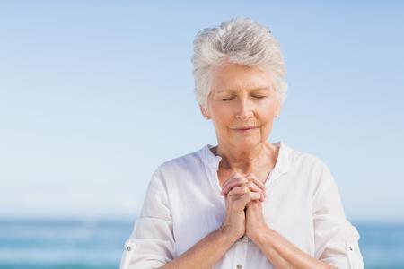 mujeres orando: Mujer mayor que ruega en la playa en un día soleado Foto de archivo