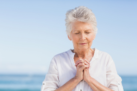 people praying: Senior woman praying on the beach on a sunny day Stock Photo