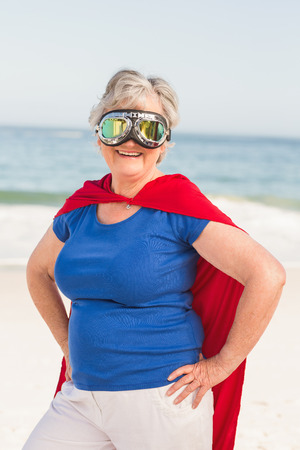 escapism: Senior woman wearing superwoman custome on a sunny day
