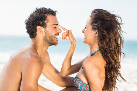 suncream: Happy girlfriend putting suncream on boyfriend on a sunny day Stock Photo