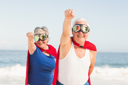 escapism: Senior couple wearing superman costume on a sunny day