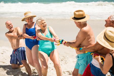 am Strand Senioren Tauziehen an einem sonnigen Tag spielen