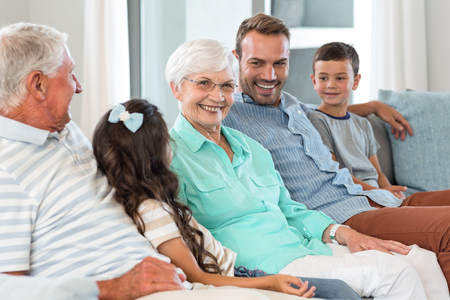 family sofa: Happy family sitting on sofa in their living room Stock Photo