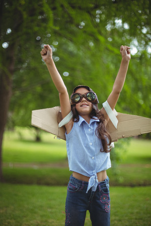 fake smile: Young girl wearing leather pilot helmet and wings pretending to fly in garden