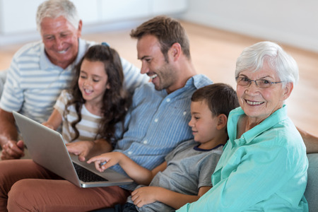 Happy family sitting on sofa using a laptop in living room