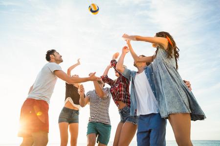pelota de voley: Friends trying to catch volley ball on a sunny day Foto de archivo