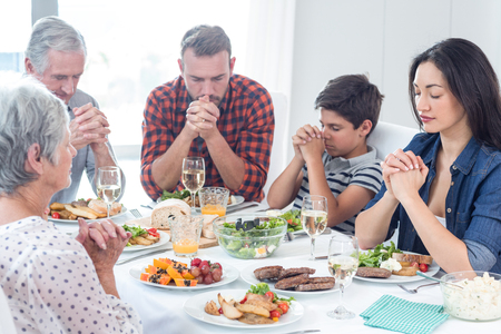 praying together: Family sitting at dining table and praying together before meal Stock Photo