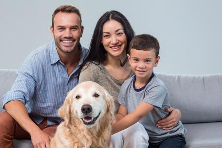 Retrato de padres felices con hijo y mascota en la sala de estar
