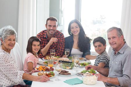 Familia sentado en la mesa de comedor que tiene comida
