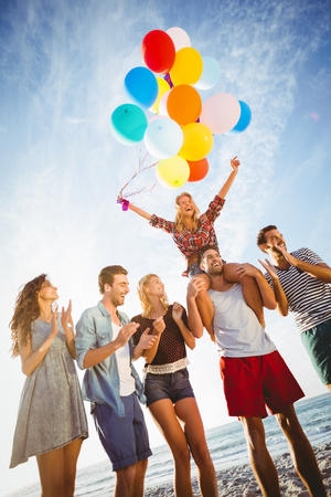 acclamation: Friends dancing on sand with balloon on a sunny day
