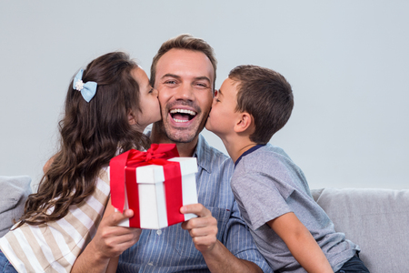 Father holding a gift and receiving kisses from son and daughter